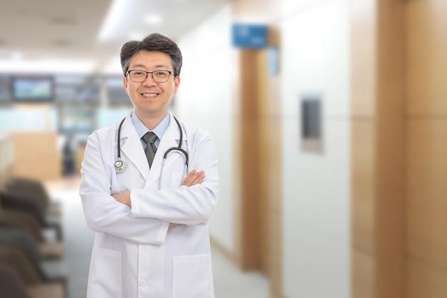 Aziatische mannelijke arts die in van het ziekenhuis glimlacht