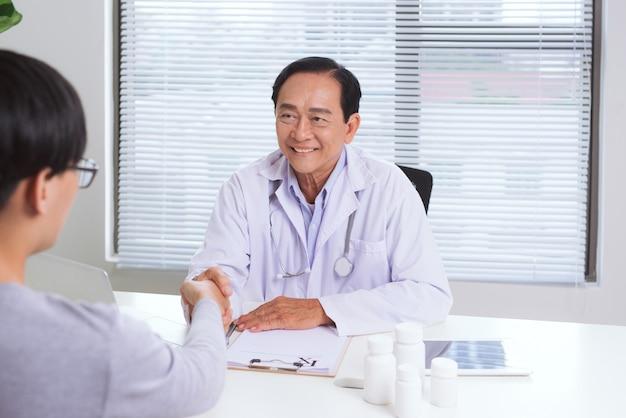 Aziatische mannelijke arts en patiënt op kantoor handen schudden, gezondheidszorg en hulpconcept