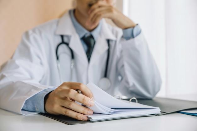 Aziatische mannelijke artsenzitting en vandaar om de kin op zijn handen te rusten en geduldige gegevens te analyseren.