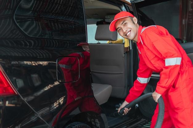 Aziatische mannelijke autoreiniger draagt rood glimlachend uniform tijdens het schoonmaken van de autovloer in de autosalon
