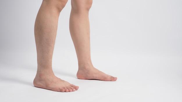 Aziatische mannelijke barefoot benen geïsoleerd op een witte achtergrond.