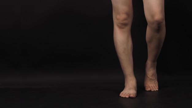 Aziatische mannelijke benen en blootsvoets is geïsoleerd op zwart background.walking concept