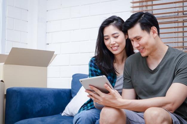 Aziatische mannelijke en vrouwelijke koppels zijn op zoek naar informatie over het online kopen van huizen