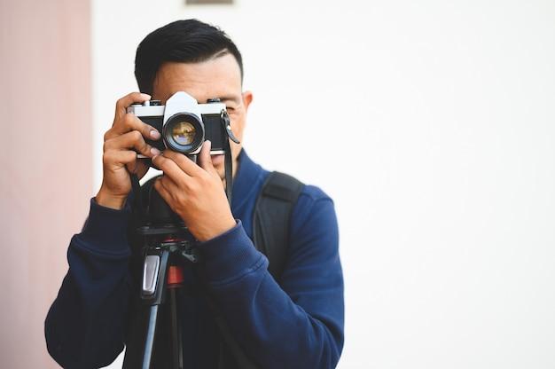 Aziatische mannelijke fotograaf die en diverse plaatsen reist fotografeert