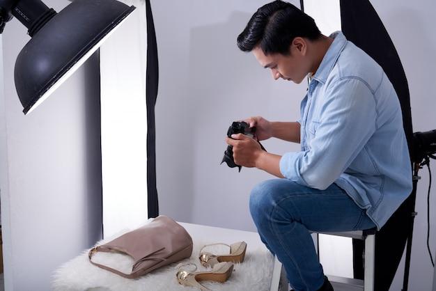 Aziatische mannelijke fotograafzitting in studio en het nemen van manier bijkomende foto's