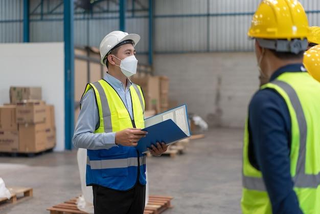 Aziatische mannelijke ingenieur met helmveiligheid en masker legt plan uit aan teamwork in magazijnfabriek