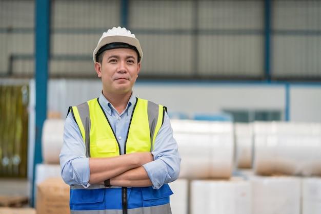 Aziatische mannelijke ingenieur met veiligheidsvest en veiligheidshelm staande met gekruiste armen in magazijnfabriek