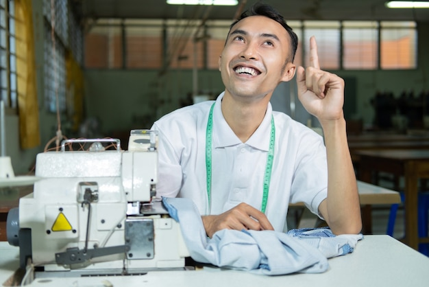 Aziatische mannelijke kleermakersglimlach met omhooggaande hand die iets wijst bij het naaien met naaimachine