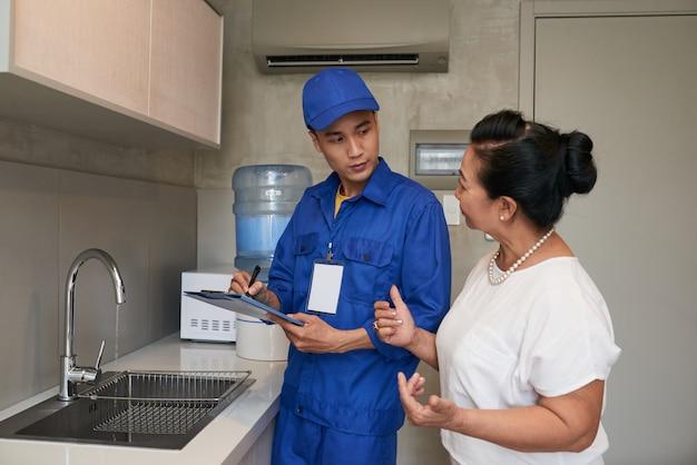 Aziatische mannelijke loodgieter in het eenvormige spreken aan hogere vrouwelijke huiseigenaar in keuken
