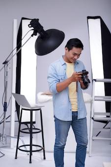 Aziatische mannelijke manierfotograaf die foto's controleren op camera in studio
