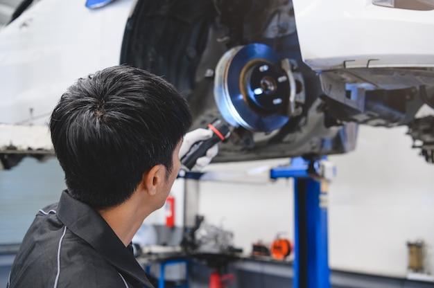 Aziatische mannelijke mechanische greep en glanzend flitslicht om het remblok van de autoschijf te onderzoeken