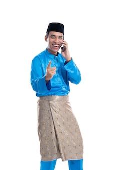 Aziatische mannelijke moslim praten over zijn telefoon op witte achtergrond