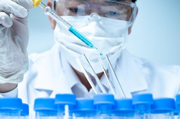 Aziatische mannelijke onderzoeker die in het laboratorium werkt.