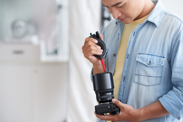 Aziatische mannelijke phographer schoonmakende cameralens met luchtventilator
