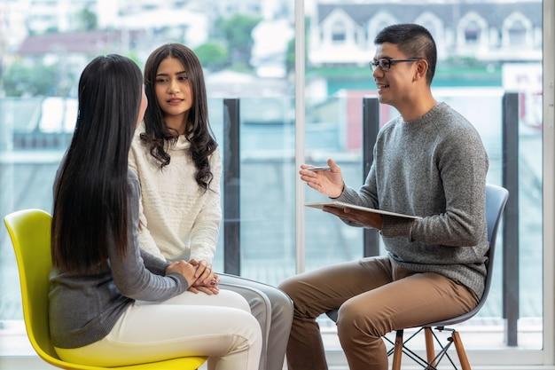 Aziatische mannelijke professionele psycholoog arts die het consult geeft aan lesbische geliefden patiënten