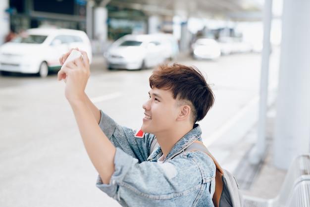 Aziatische mannelijke reiziger die foto neemt tijdens het wachten op een taxi op de luchthaven