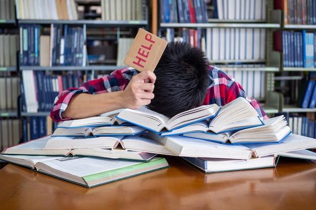 Aziatische mannelijke student is moe en gestrest voor de voorbereiding op het examen