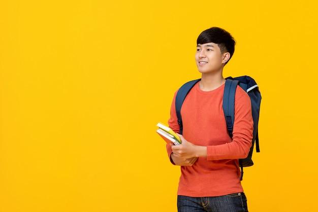 Aziatische mannelijke student met boeken van de rugzakholding