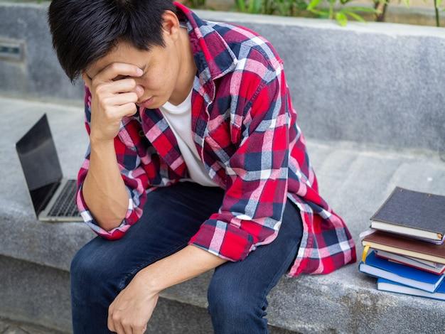 Aziatische mannelijke studenten waren teleurgesteld over de resultaten van het toelatingsexamen voor de universiteit. verdriet en overstuur