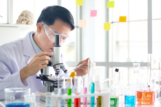 Aziatische mannelijke wetenschapper kijkt door de microscoop in het laboratorium.