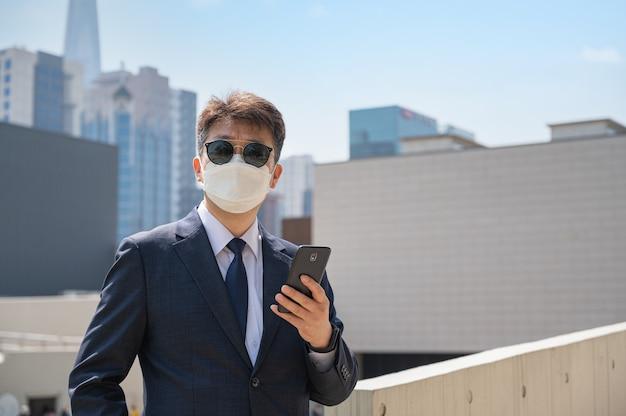 Aziatische mannelijke zakenman die smartphone houdt die zonnebril en masker in de stad draagt.