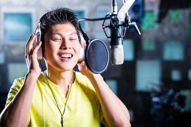 Aziatische mannelijke zanger die lied in opnamestudio produceert