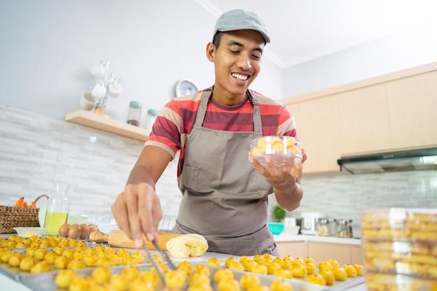 Aziatische mannelijke zelfgemaakte cake portret van jonge man zet nastar cake op een plastic doos
