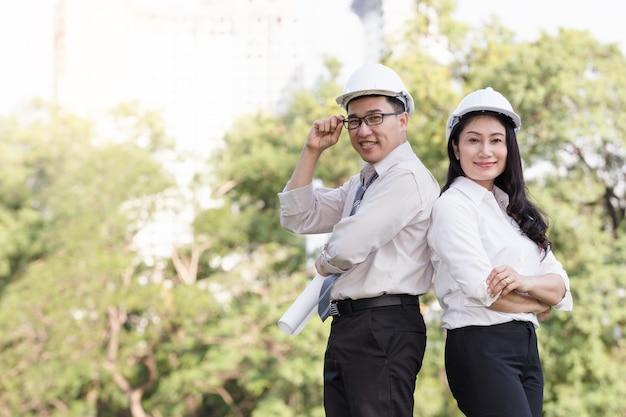 Aziatische mannen en vrouweningenieurs werken aan plannenbouw in het park