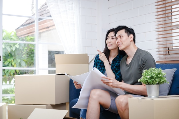 Aziatische mannen- en vrouwenparen houd de blauwdruk vast, het nieuwe huis is blij om samen een gezin te stichten.