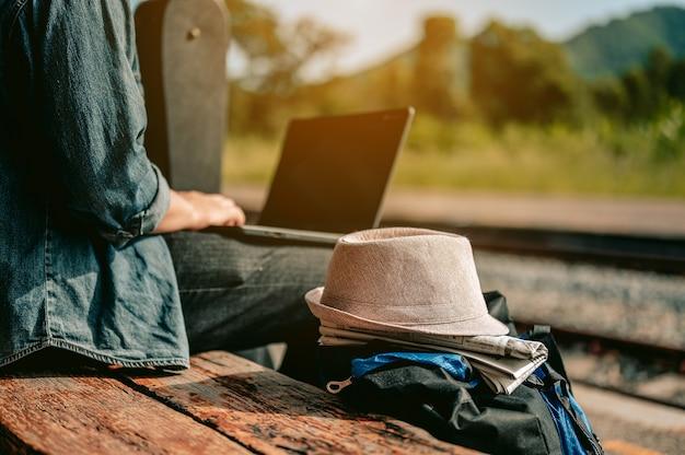 Aziatische mannen gebruiken hun laptop om te werken terwijl ze wachten om aan boord van de trein te gaanvakantiereisreis