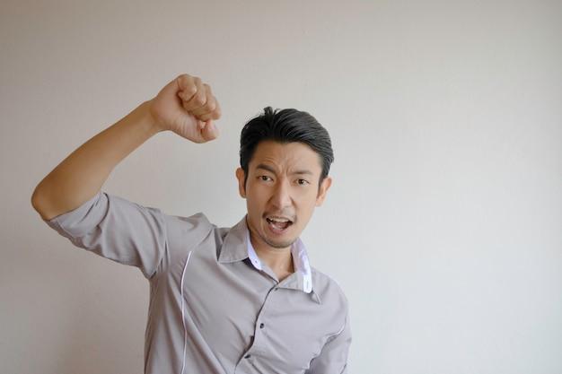 Aziatische mannen met grijze shirts vuist in de rechterhand steken tekenen van vreugde tonen