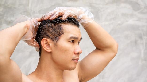Aziatische mannen verven zijn haarkleur op een grijze achtergrond.