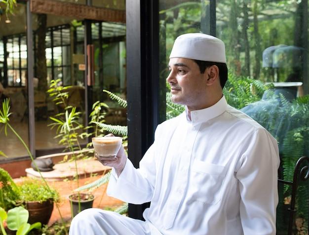 Aziatische medio oude moslim zakenman zitten in coffeeshop drinken koffie met mobiele telefoon op tafel.