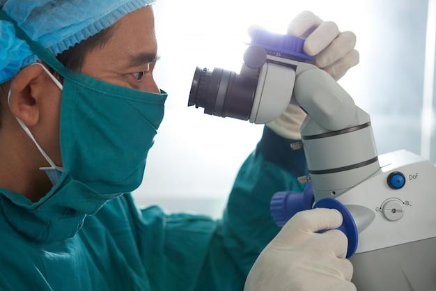 Aziatische medische onderzoeker in beschermende schort, masker, hoed en handschoenen die in microscoop turen