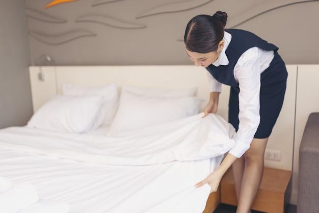 Aziatische meid die bed in hotelkamer maakt, hoofdkussen op bed opzet