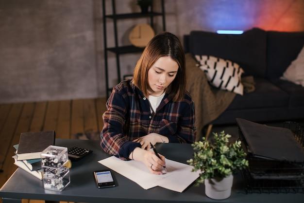 Aziatische meisje handelaar thuis werken aan de tafel, de grafiek bestuderen