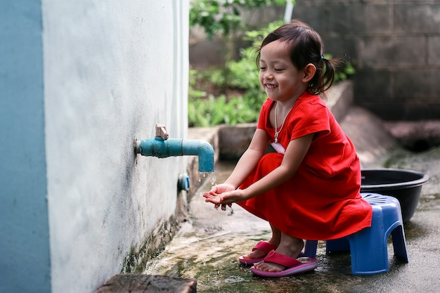 Aziatische meisje handen wassen thuis