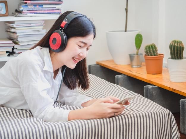 Aziatische meisje het luisteren muziek in hoofdtelefoons op bed