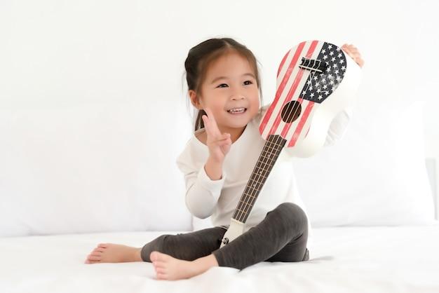 Aziatische meisje het spelen ukelele in slaapkamer