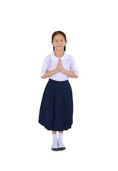 Aziatische meisje kind in thaise schooluniform bidden en staan geïsoleerd op een witte achtergrond. afbeelding volledige lengte met uitknippad