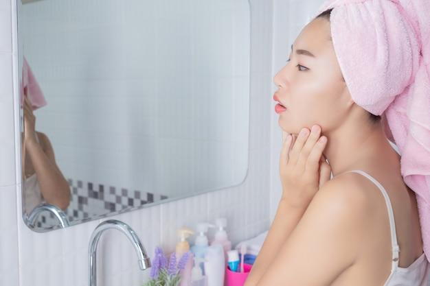 Aziatische meisje knijpt acne.