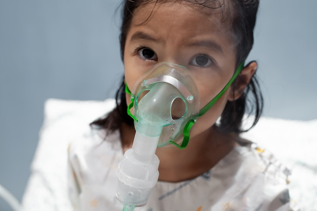 Aziatische meisje moet verneveling door inhalator masker op haar gezicht krijgen