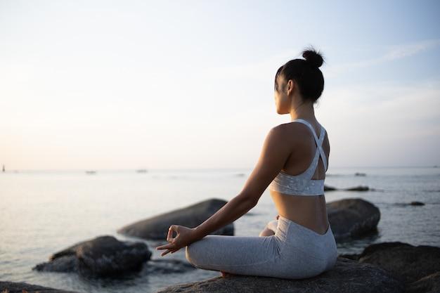 Aziatische meisje praktijk yoga op het strand sunrise ochtend dag