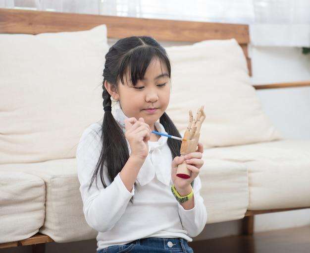 Aziatische meisje verf houten pop thuis