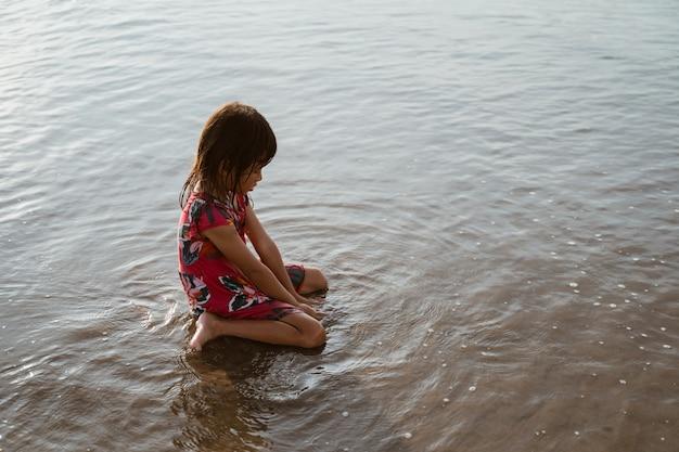 Aziatische meisje zittend op zand in het strand tijdens het spelen met water
