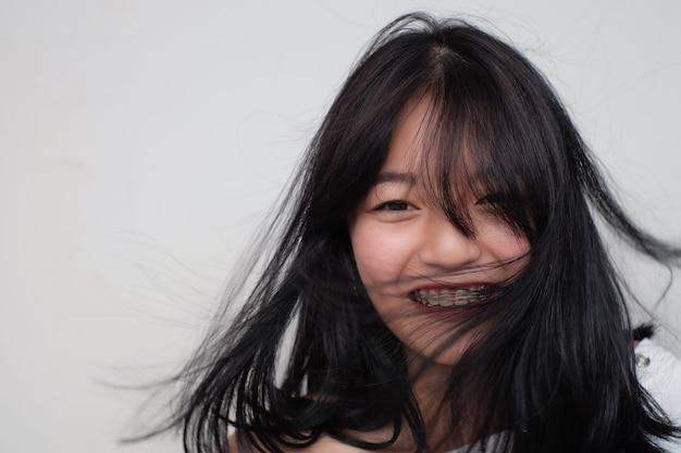 Aziatische meisjeglimlach met palhulpmiddel
