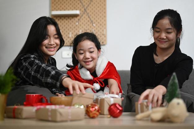 Aziatische meisjes bereiden zich voor op kerstmis en pakken cadeautjes samen thuis in.