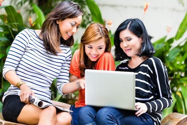 Aziatische meisjes die een notitieboekje gebruiken
