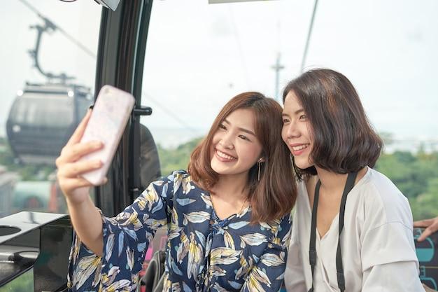 Aziatische meisjes die een selfiefoto samen met haar vriend in kabelwagen nemen. kabelwagen rijden.