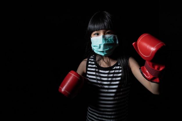 Aziatische meisjes dragen gezichtsmaskers als bescherming tegen virussen en bokshandschoenen als symbool voor de bestrijding van virussen als coronavirus